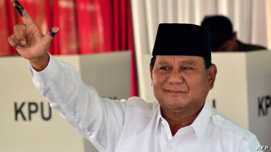 Presidential challenger Prabowo Subianto shows off his ink-dyed finger after casting his vote in Indonesia's general election at a polling station in Bogor, April 17, 2019.