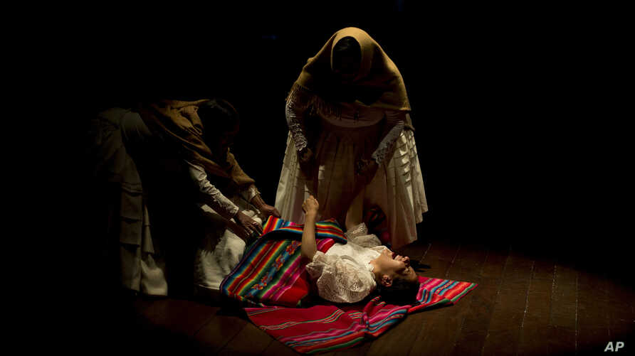 In this April 30, 2019 photo, the spotlight shines on a group of women vendors turned actors who recount stories of gender-based violence, at the Municipal theater of La Paz, Bolivia.