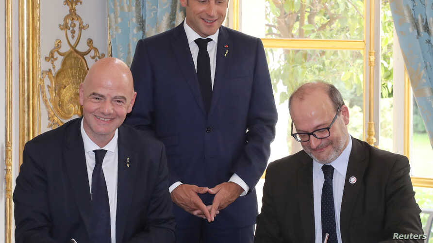 French president Emmanuel Macron stands during the signature of an agreement between FIFA president Gianni Infantino and AFD (French Development Agency) president Remy Rioux at the Elysee Palace, in Paris, June 4, 2019.