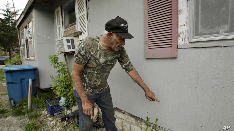 FILE - Elmer Sullivan shows the height of floodwater on one of the many times his house has flooded in the small community of Mosby, Missouri, April 24, 2019.