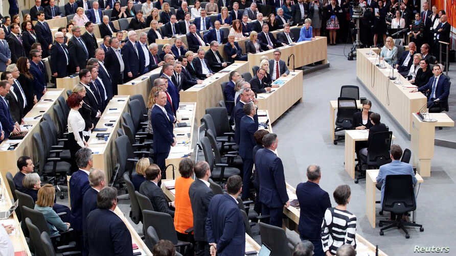Members of the Parliament stand during a session of the Parliament in Vienna, Austria, May 27, 2019.