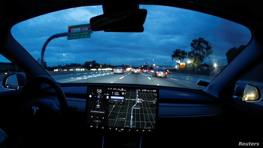 A Model 3 Tesla vehicle navigates morning rush hour using the car's auto pilot feature in Los Angeles, California, March 20, 2019.