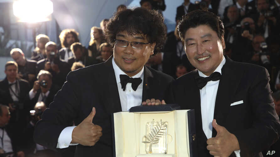 """Actor Kang-Ho Song, right, and director Bong Joon-ho pose with the Palme d'Or award for the film """"Parasite"""" following the awards ceremony at the 72nd international film festival in Cannes, France, May 25, 2019."""
