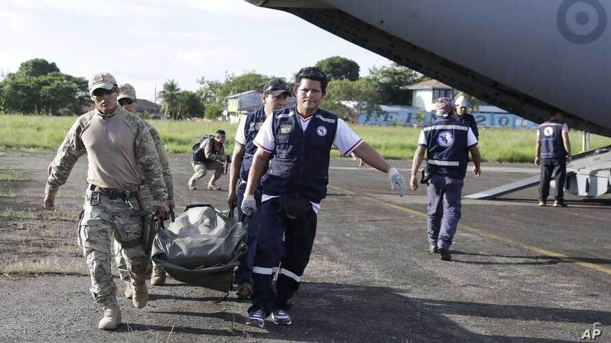Soldiers and health brigade members carry equipment from a plane to be used in areas affected by an earthquake in Yurimaguas, Peru, May 26, 2019
