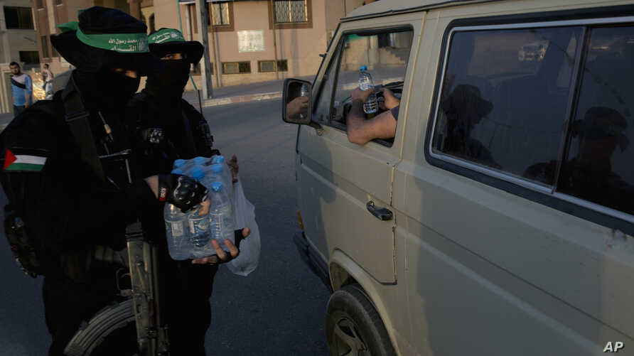 Masked Hamas gunmen give out water to motorists in Gaza City just minutes before breaking fast, during the Muslim holy month of Ramadan, May 16, 2019.