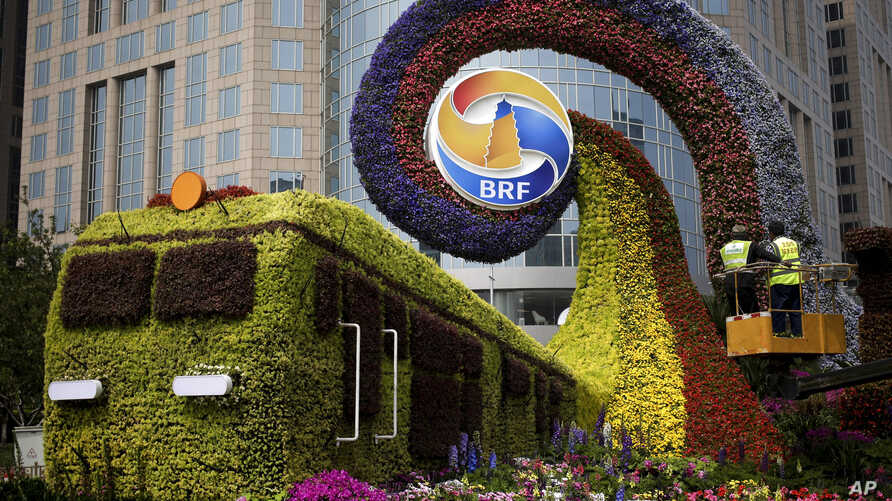 Workers on a platform install flowers on a display in a shape of a train to promoting the upcoming Belt and Road Forum in Beijing, China, April 23, 2019.
