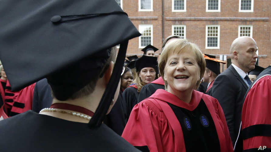 German Chancellor Angela Merkel greets graduating Harvard students as she walks in a procession though Harvard Yard at the start of Harvard University commencement exercises, May 30, 2019, in Cambridge, Mass.