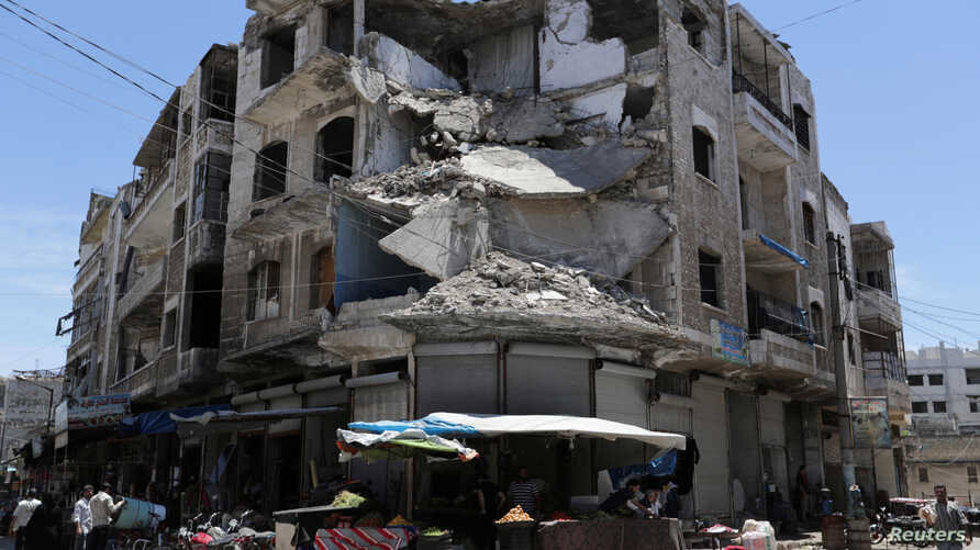 FILE - People walk past a damaged building in the city of Idlib, Syria, May 25, 2019.