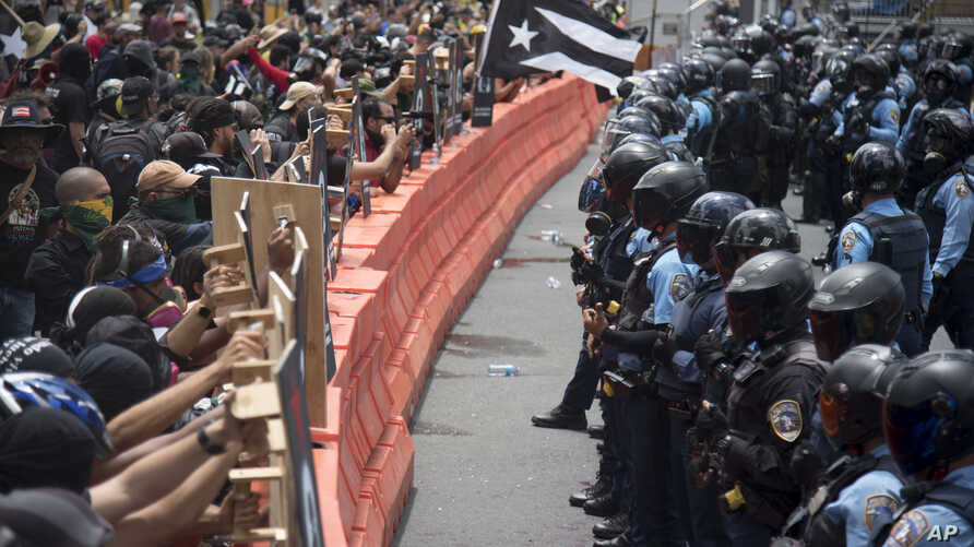 Demonstrators holding wooden shields are confronted by police during a protest against the Federal Fiscal Control Board, as part of the May Day celebration in San Juan, Puerto Rico, May 1, 2019.