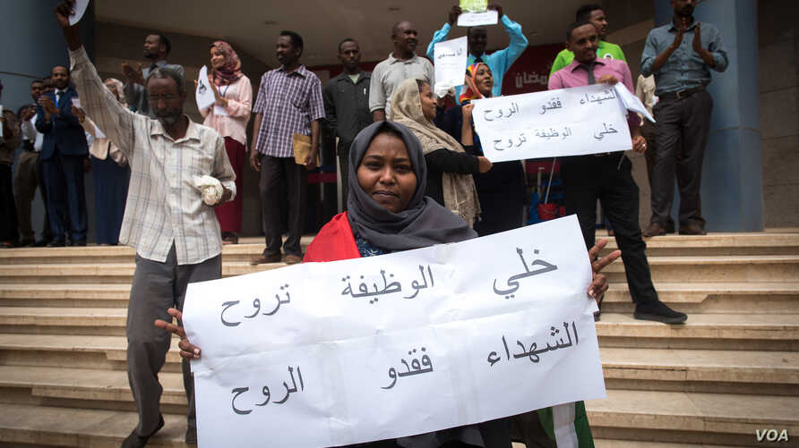 Susana Abdalla Hassan, an employee of Bank of Khartoum, holds a sign supporting the revolution while striking outside Al-Waha mall, in Khartoum, Sudan, May 28, 2019.