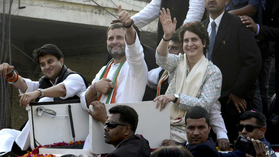 India's Congress party President Rahul Gandhi, center, gestures with the party's general secretaries Priyanka Gandhi Vadra, right, and Jyotiraditya Scindia, left, by his side during a rally in Lucknow, India, Feb. 11, 2019.