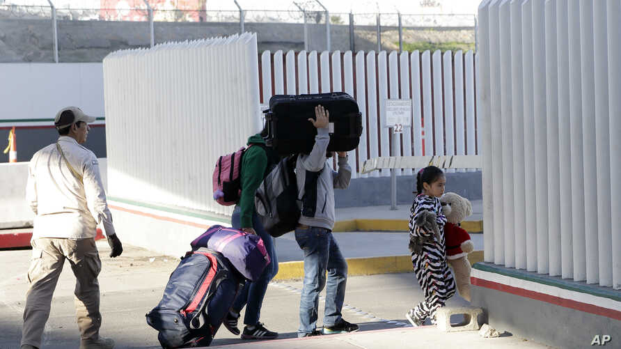 A family leaves to apply for asylum in the United States, at the border, Jan. 25, 2019, in Tijuana, Mexico.