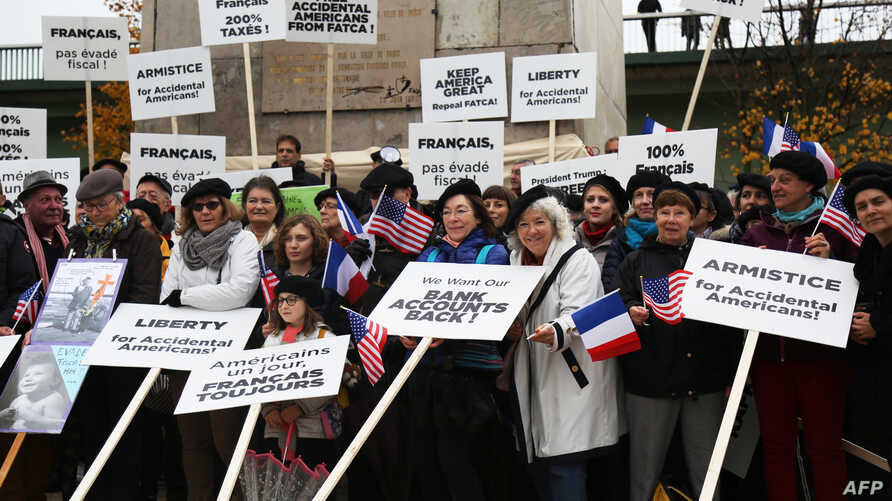 Protesters hold placards as they take part in a demonstration by the Association des Americains Accidentels (AAA - Accidental Americans Association) to alert the US president on their situation, as he is in Paris to attend World War I armistice centenary commemorations, at the base of the Paris Statue of Liberty on the Iles aux Cygnes in the river Seine in Paris on November 11, 2018.