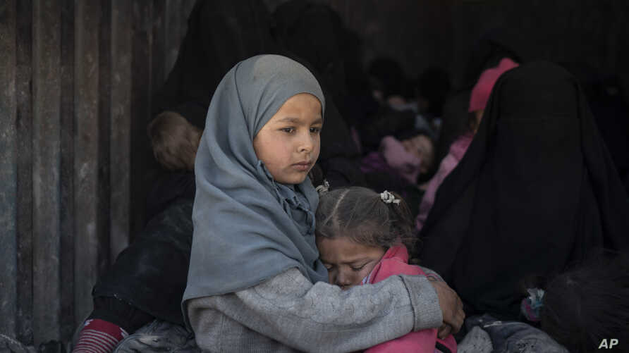 Children ride in the back of a truck that is part of a convoy evacuating hundreds out of the last territory held by Islamic State militants, in Baghouz, eastern Syria, Feb. 20, 2019.