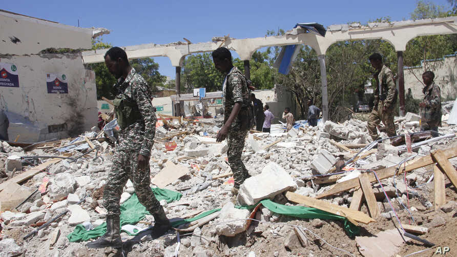 Somali soldiers walk near a destroyed building after a car bomb in Mogadishu, May 14, 2019.