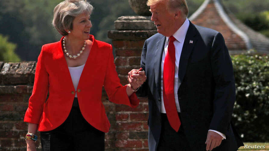 FILE - Britain's Prime Minister Theresa May and U.S. President Donald Trump walk to a joint news conference at Chequers, the official country residence of the prime minister, near Aylesbury, Britain, July 13, 2018.