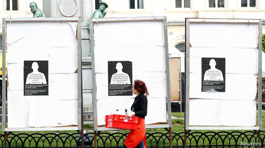 A woman walks past election campaign billboards in front of the European Parliament in Brussels, Belgium, April 30, 2019.