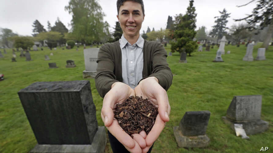 FILE - Katrina Spade, the founder and CEO of Recompose, a company that hopes to use composting as an alternative to burying or cremating human remains, poses for a photo in a cemetery in Seattle as she displays a sample of compost material left from ...