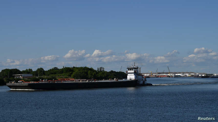 A barge travels through the Houston Ship Channel, part of the Port of Houston, in Pasadena, Texas, May 5, 2019.