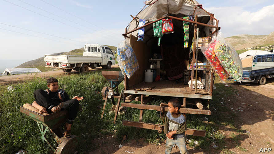 Syrian children whose families fled the western countryside of Hama are pictured in front of a temporary home in a makeshift camp in Sher Maghar in Hama province, April 27, 2019. Syrian troops' push into the rebel-held enclaveKfarNabudah on May 8...