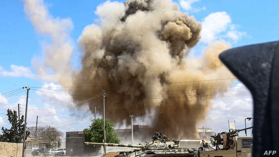 A smoke plume rises from an airstrike behind a tank and technicals (pickup trucks mounted with turrets) belonging to forces loyal to Libya's Government of National Accord during clashes in the suburb of Wadi Rabie, south of the capital Tripoli, April...