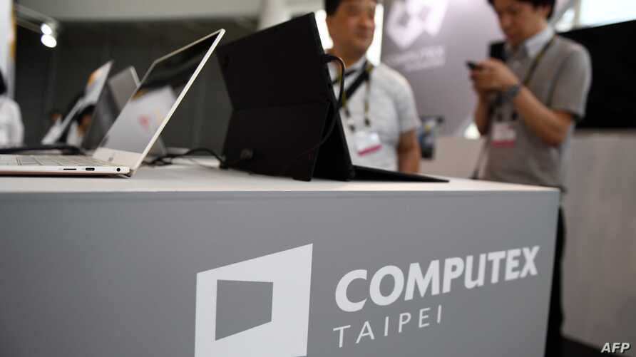 FILE - Visitors stand behind a desk with the Computex logo during Computex 2018, at the Nangang Exhibition Center in Taipei, Taiwan, June 5, 2018.