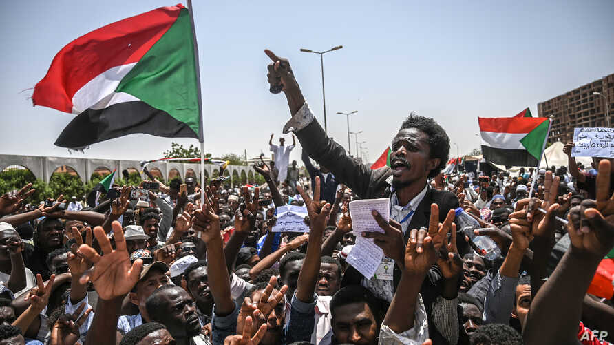 Sudanese protesters wave national flags as they chant slogans during a sit-in outside the army headquarters in the capital Khartoum, April 26, 2019.