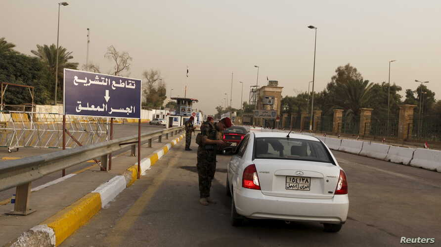 FILE - Iraqi security forces search vehicles at a checkpoint as cars cross into the Green Zone in Baghdad, Iraq, Oct. 5, 2015. The zone houses government buildings and foreign embassies, including that of the United States.
