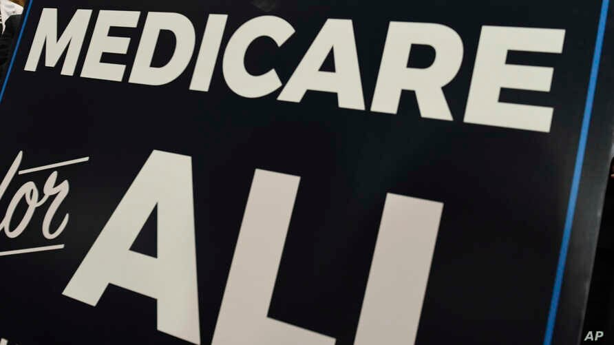 """FILE - A sign is shown during a news conference to reintroduce  """"Medicare for All"""" legislation, on Capitol Hill in Washington, April 10, 2019."""