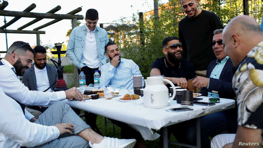 """Guests from places within Denmark and Northern Europe sit together at the engagement party of a resident in Mjolnerparken, a housing estate on the Danish government's """"Ghetto List,"""" in Copenhagen, Denmark, May 6, 2018."""