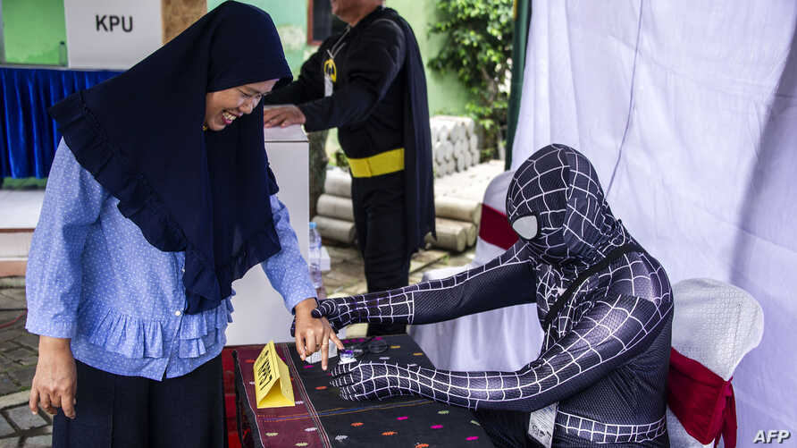 Indonesian election workers dressed in superhero costumes register voters at a polling station in Surabaya, April 17, 2019.