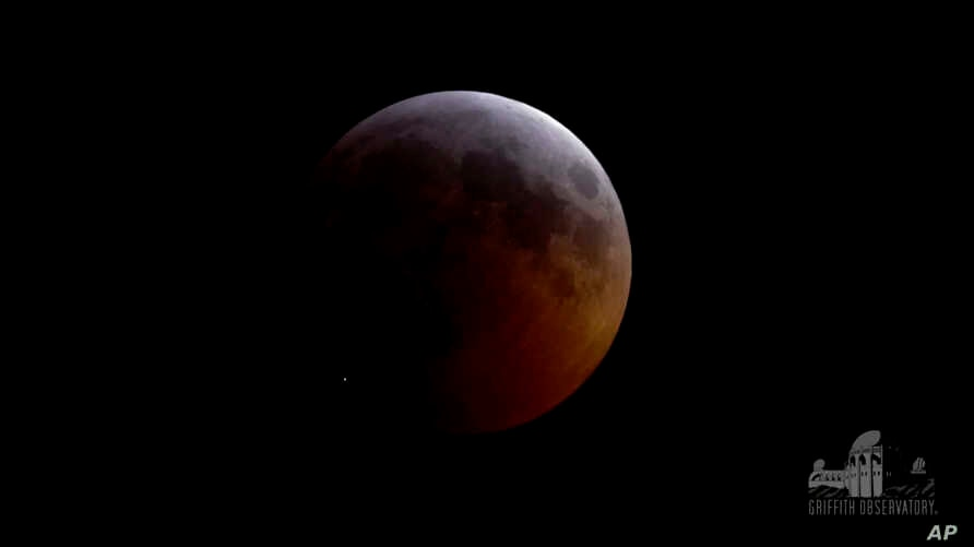FILE - This image from video provided by Griffith Observatory in Los Angeles shows an impact flash on the moon (Bottom-L) during the lunar eclipse which started on Jan. 20, 2019.