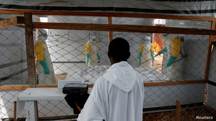 FILE - A priest watches as health workers dressed in Ebola protective suits prepare the body of an Ebola patient for burial at the Ebola treatment center in Butembo, in the Democratic Republic of Congo, March 26, 2019.