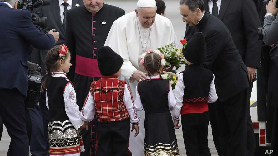 Pope Francis is welcomed by children wearing traditional dresses upon his arrival in Sofia, Bulgaria, May 5, 2019. Pope Francis is visiting Bulgaria, the European Union's poorest country and one that taken a hard line against migrants, a stance that ...