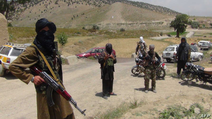 FILE - Fighters with Afghanistan's Taliban militia stand with their weapons in Ahmad Aba district on the outskirts of Gardez, the capital of Paktia province, on July 18, 2017.