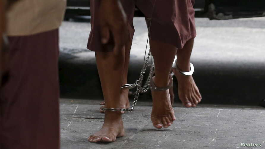 FILE - The shackled legs of suspected human traffickers are seen as they arrive for their trial at the criminal court in Bangkok, Thailand, March 15, 2016.