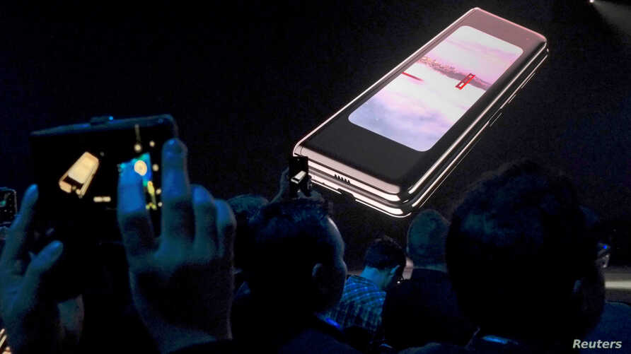 FILE - The Samsung Galaxy Fold phone is shown on a screen at Samsung Electronics Co. Ltd.'s Unpacked event in San Francisco, Feb. 20, 2019. Samsung says it will look into some reports of flickering or cracking screens.