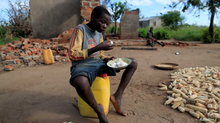 """Bernado Jofresse, 14, eats rice for breakfast as he sits beside his family's damaged house in the aftermath of Cyclone Idai, in the village of Cheia, which means """"Flood"""" in Portuguese, near Beira, Mozambique, April 3, 2019."""