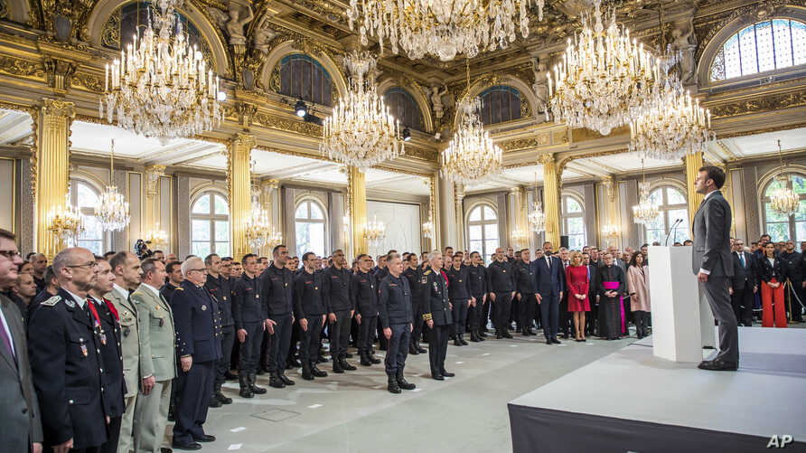 French President Emmanuel Macron stands at attention after addressing Paris Firefighters' brigade and security forces who took part at the fire extinguishing operations of the Notre Dame of Paris Cathedral fire, at the Elysee Palace in Paris, April 1...