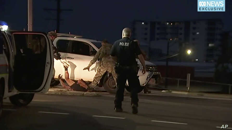 In this image made from video, police proceed to apprehend a suspect on the ground next to a white truck, June 4, 2019, in Darwin Australia. (Australian Broadcasting Corporation via AP)