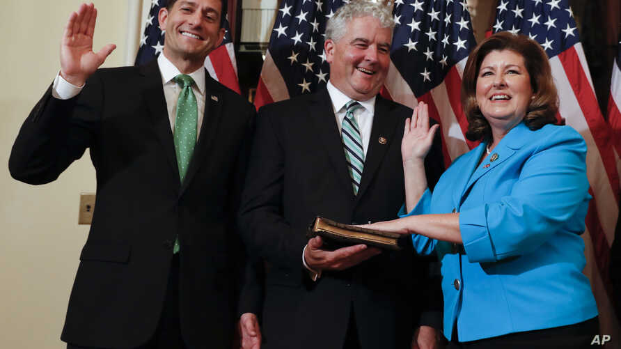 FILE - Speaker of the House Paul Ryan, R-Wis. (L), Representative-elect Karen Handel, R-Ga.(R), and her husband Steve Handel participate in a ceremonial swearing-in on Capitol Hill in Washington, June 26, 2017.