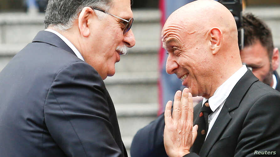FILE - Faiez Mustafa Serraj, President of the Presidency Council of the Government of National Accord of Libya (L), is greeted by Italian Interior Minister Marco Minniti during a meeting in Rome, Italy, March 20, 2017.