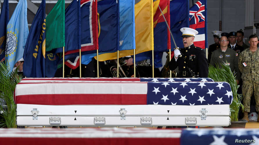 FILE - An honor guard signals a command as caskets containing the remains of American servicemen from the Korean War handed over by North Korea arrive at Joint Base Pearl Harbor-Hickam in Honolulu, Hawaii, U.S., Aug. 1, 2018.