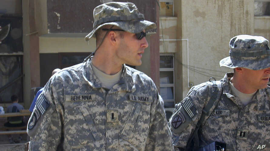 FILE - 1st Lt. Michael C. Behenna, left, and his defense attorney Capt. Tom Clark, right, walk in Camp Speicher, a large U.S. base near Tikrit, north of Baghdad, Iraq, Sept. 21, 2008.