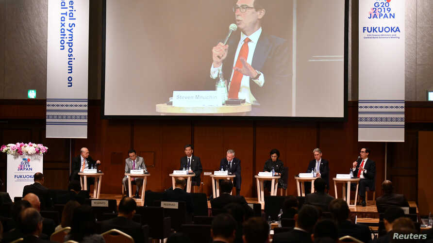 U.S. Secretary of Treasury Steven Mnuchin, right, on podium, delivers a speech during the G20 Ministerial Symposium on International Taxation in the G20 Finance Ministers and Central Bank Governors meeting in Fukuoka, Japan, June 8, 2019.