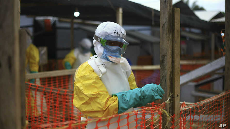 FILE - An Ebola health worker is seen at a treatment center in Beni, Eastern Congo, April, 16, 2019. The World Health Organization is warning it may not be possible to contain Ebola to the two affected provinces in eastern Congo if violent attacks on heal