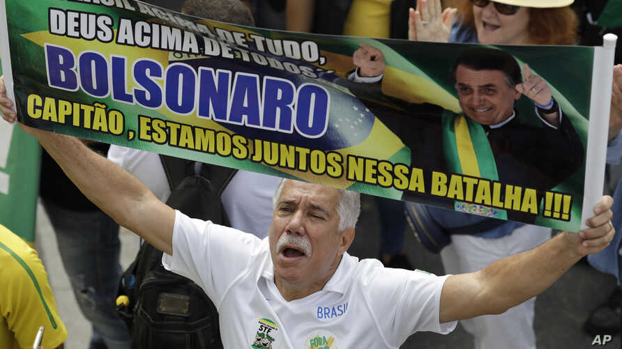 "A supporter of Brazil's President Jair Bolsonaro holds up a message in Portuguese: ""Bolsonaro, captain, we are in this battle together,"" on Copacabana beach in Rio de Janeiro, Brazil, May 26, 2019."