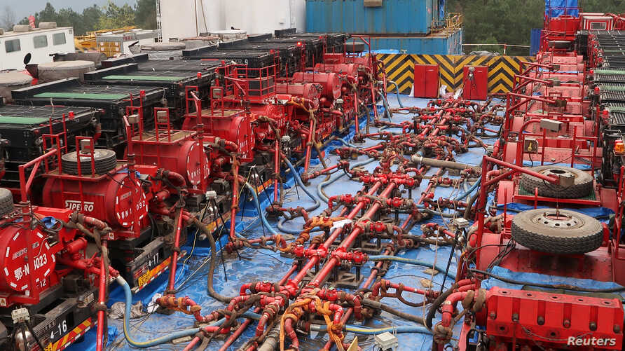 Fracking trucks at work are seen at a shale gas well of Sinopec in Nanchuan, Chongqing, China March 18, 2018. Picture taken March 18, 2018.  REUTERS/Chen Aizhu - RC11DF239C00