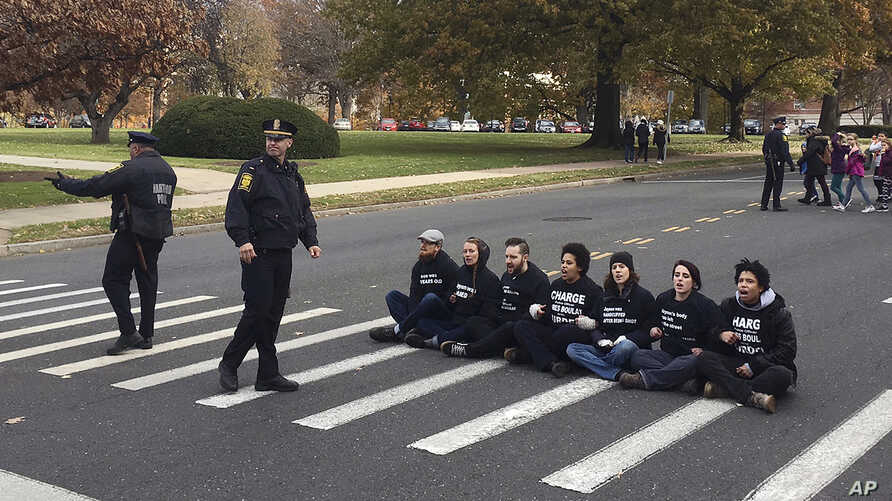 FILE - People sit in a street outside the state Capitol in Hartford, Conn., Nov. 27, 2017, to demonstrate the handling of the case of Jayson Negron, 15, killed by police in May in Bridgeport.