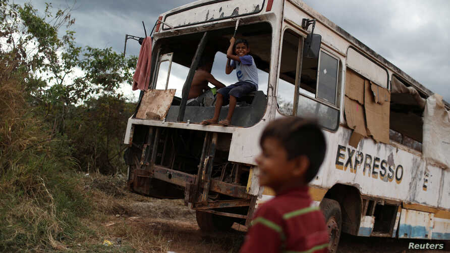 Venezuelan Erasmo Valderrama plays with a friend on an abandoned bus in the border city of Pacaraima, Brazil, April 13, 2019.